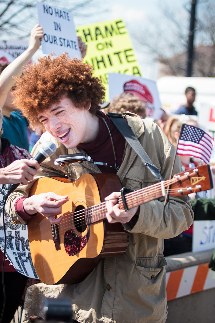 Battle of the bands: the protesters against Trump featured a young musician singing classics by Bob Dylan, Woody Guthrie, and Peter, Paul And Mary.