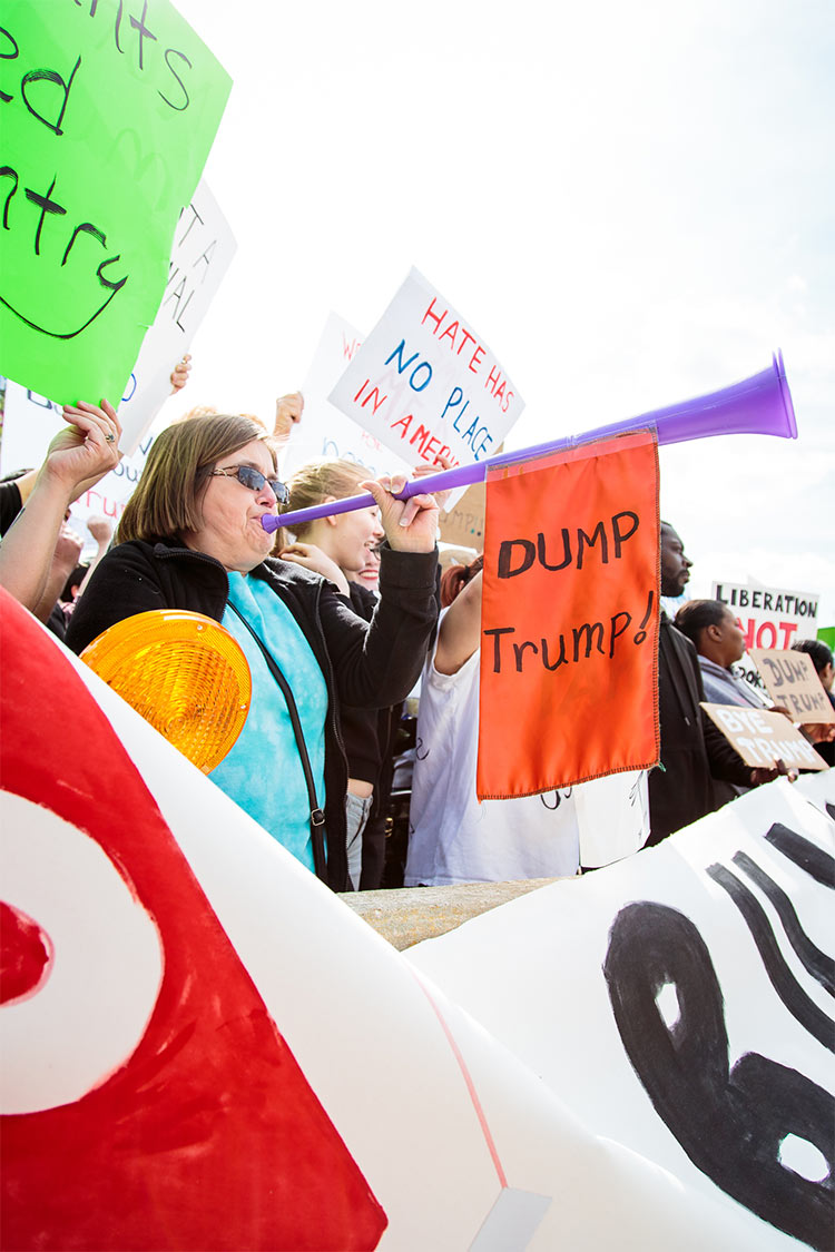 """Protesters were corralled into a """"Free Speech Zone,"""" separated from the long line of people waiting to get into the rally. Trump's campaign has earned a reputation of violence, with Trump encouraging his supporters to aggressively eject protesters. As Trump was arriving in Wisconsin, his campaign manager was charged with simple battery for an incident earlier in the month."""